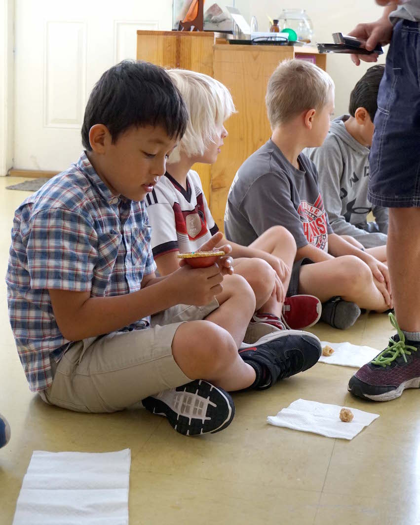 This Lower Elementary student observes a diyas as the sweet is passed around the classroom.