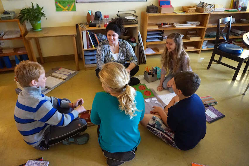 Miss Jess works on a math lesson with a group of students in the Upper Elementary classroom.