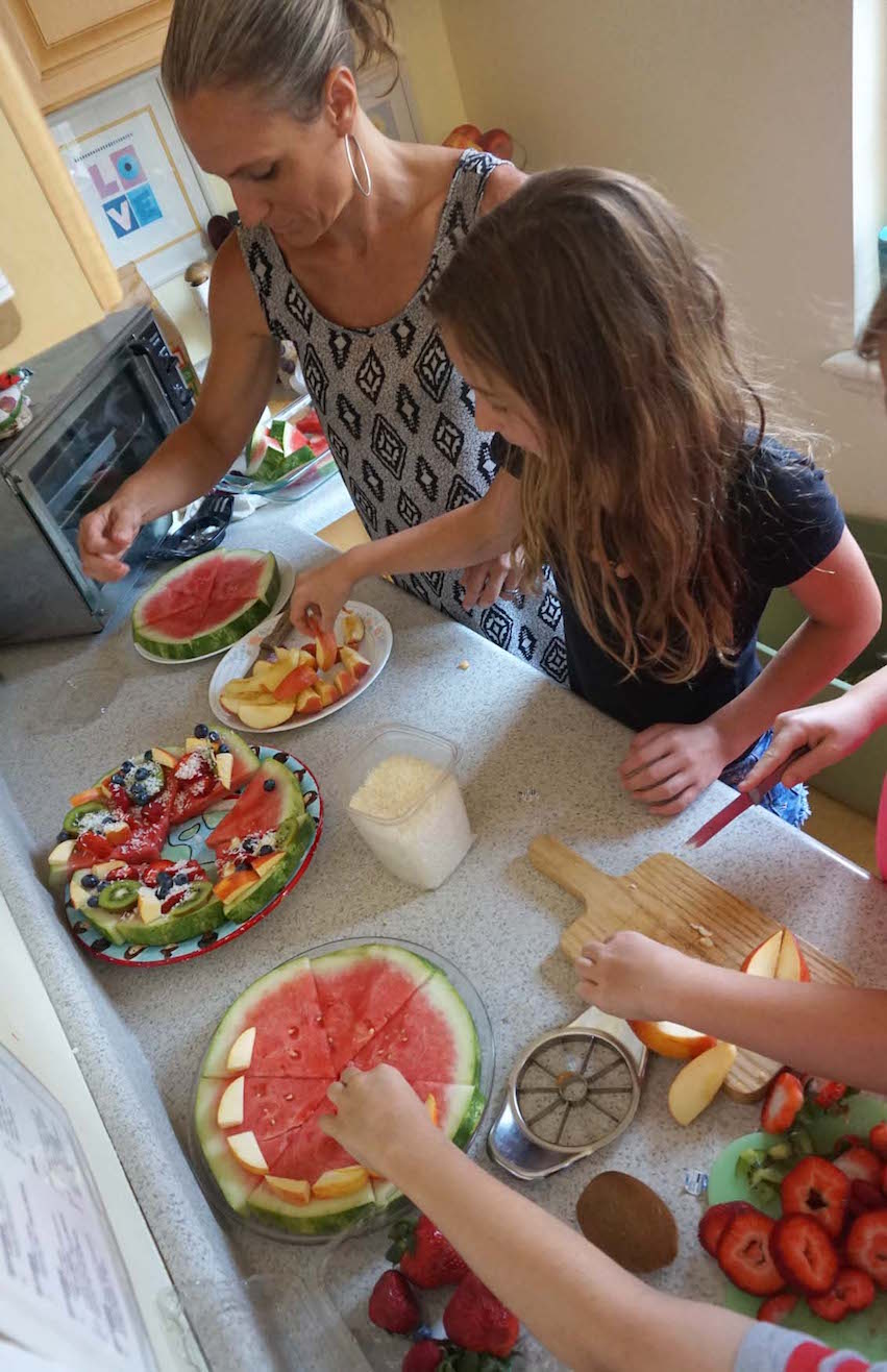 Miss Ashley helps a group of Lower Elementary students prepare fruit pizzas during a cooking session.