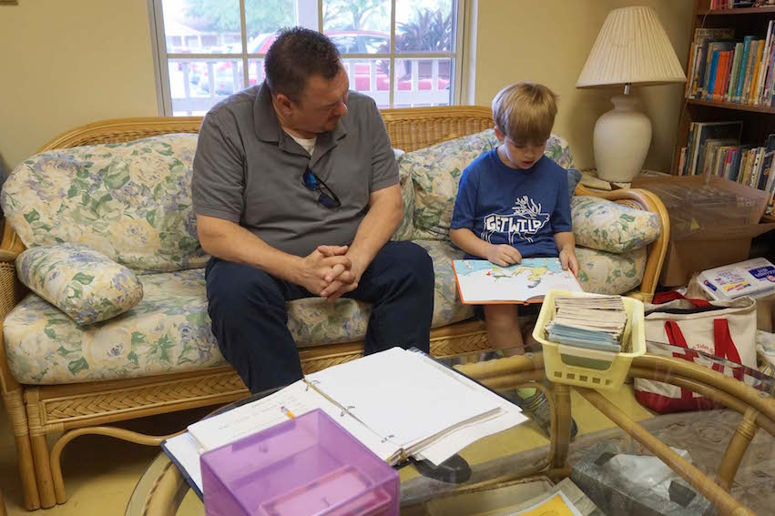 Mr. Bill reads with a Lower Elementary student. Parent readers volunteer to listen to and read with students.