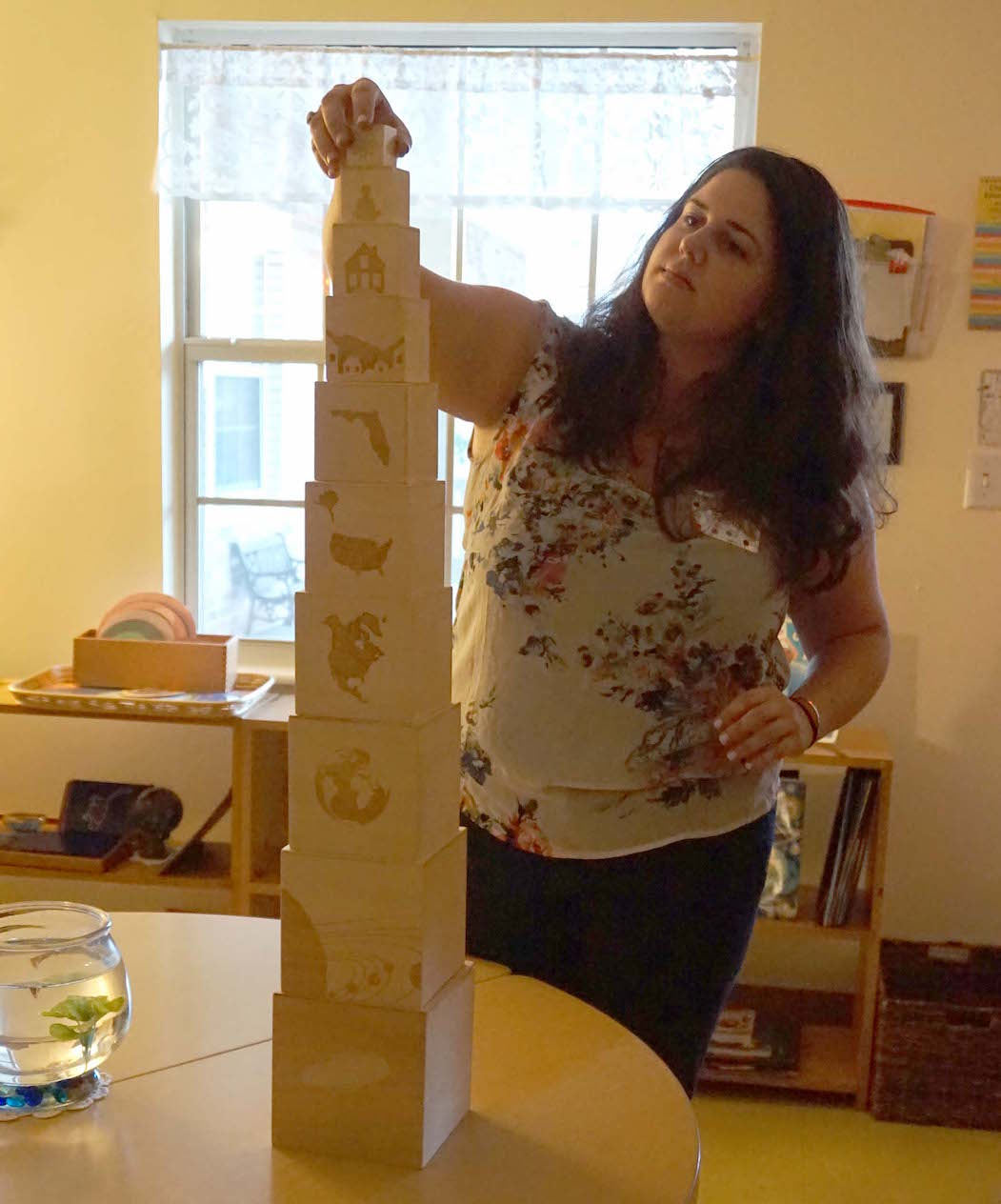 Miss Jess, who teaches in the Upper Elementary classroom, places the final block on a block tower that helps students to visualize their places in the universe.