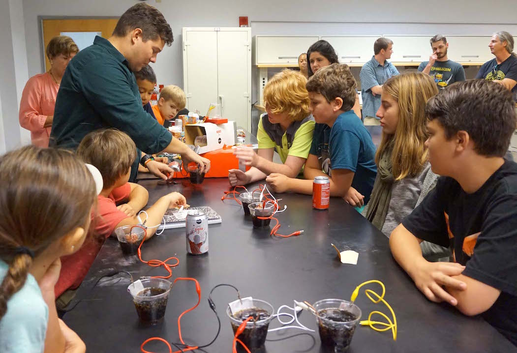 Dr. Steve Stagon, a mechanical engineering professor and MTS parent, works with the students on their soda can battery in a UNF lab.