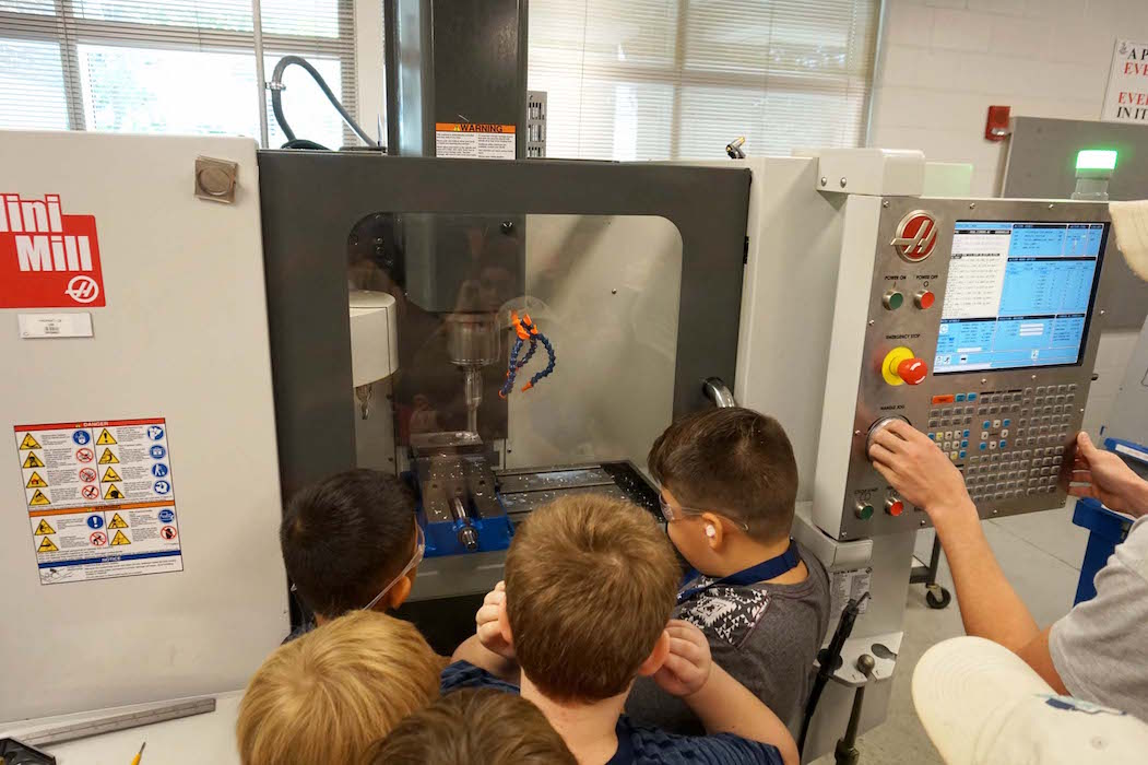 The students watch a machine cut a piece of metal in the manufacturing lab during their tour of UNF.