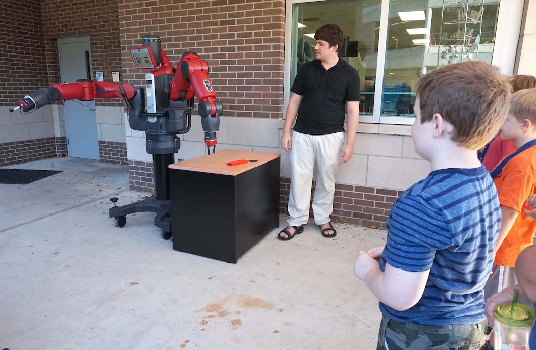 Baxter, a humanoid robot with an iPad face, demonstrates his abilities to the group of MTS students during their visit. Baxter was able to pick up and release the red block on the table.
