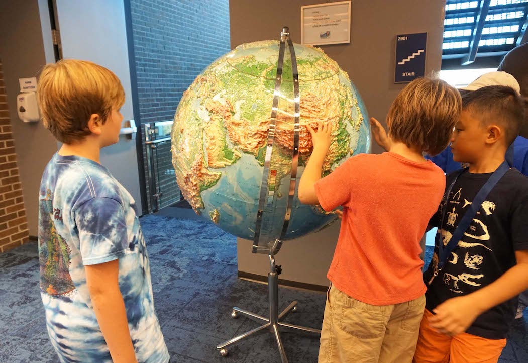 A group of MTS students checks out a large topographical globe during a visit to the library on the UNF field trip.