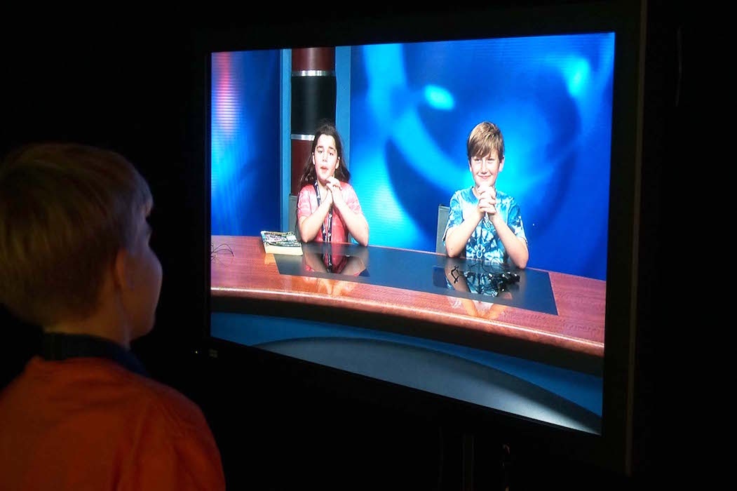 A Lower Elementary student watches the TV screen showing two MTS students sitting at the anchor desk in the TV studio.