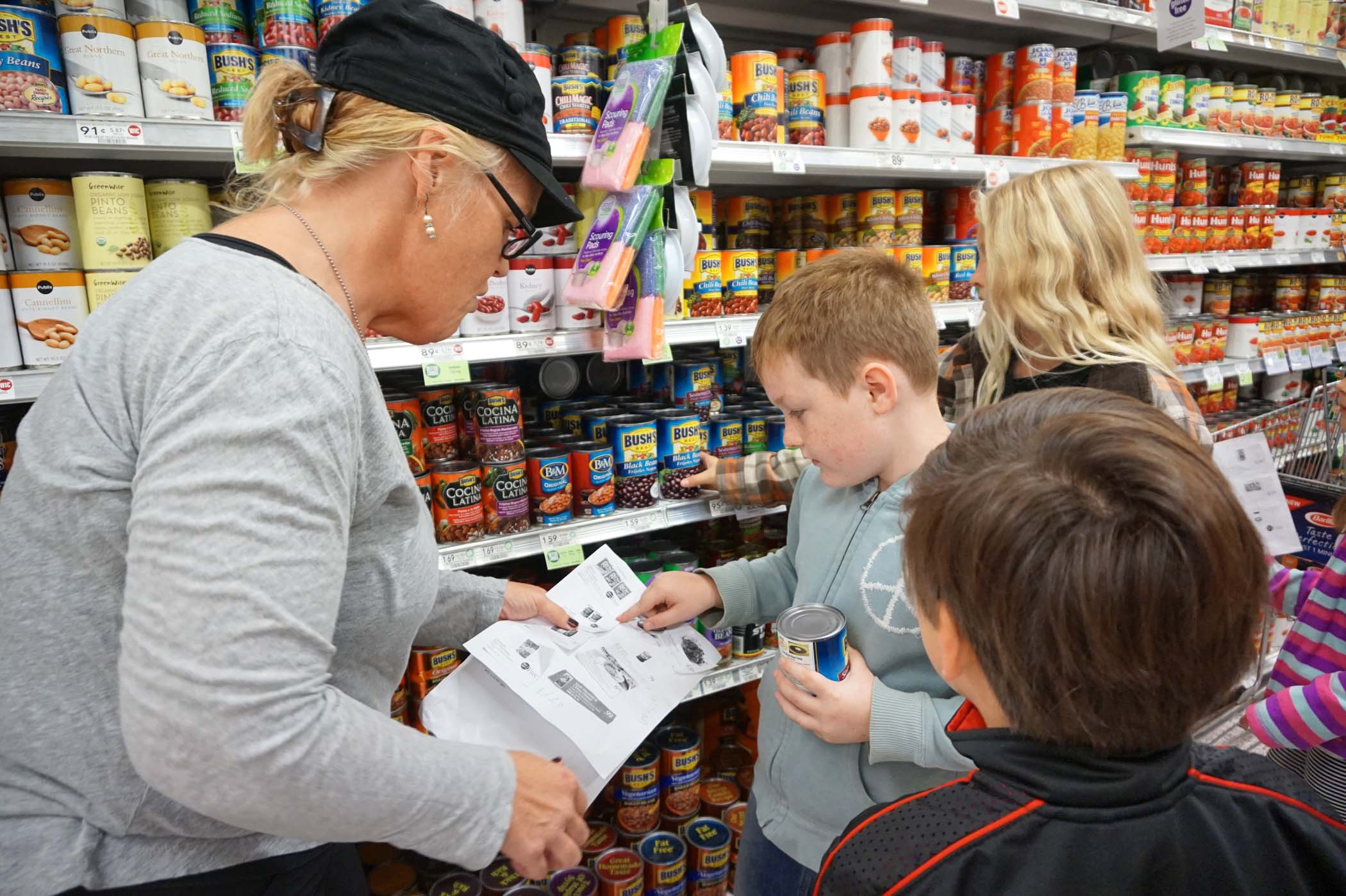 A parent chaperone and students look over a meal plan they created as they shop for food to donate to the USO Mayport Center in the school's 14th annual USO food drive.